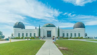 Cinematic 4K time lapse in motion or hyper-lapse of Griffith Observatory Park entrance in Los Angeles, California on a sunny, blue sky day.