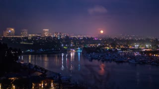 Cinematic 4K time lapse of the moon rising over the Newport Beach city skyline and harbor with Fashion Island on the horizon
