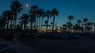 Cinematic 4K urban time lapse in motion (hyper lapse) at Balboa Pier in Newport Beach, California during gorgeous early morning sunrise facing the city with palm trees and cars in parking lot