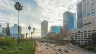 Cinematic freeway traffic view in downtown Los Angeles. Shot as a motion timelapse or hyperlapse walking with skyscrapers and palm trees on partially cloudy early morning.