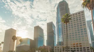 Cinematic motion timelapse or hyperlapse of downtown Los Angeles city high rise buildings at sunrise with fast moving clouds above and palm trees.