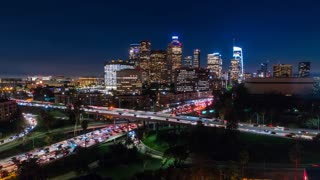 Cinematic urban aerial hyperlapse of downtown Los Angeles freeways with heavy traffic, city skyline and sky scrapers at night.