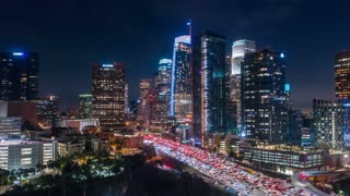 Cinematic urban aerial hyperlapse of downtown Los Angeles freeways with heavy traffic, stunning city skyline and skyscrapers with deep blue sky.