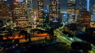 Cinematic urban aerial shot of downtown Los Angeles with freeway traffic and skyscrapers at night.