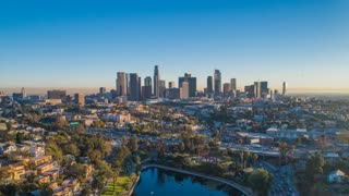 Cinematic urban aerial time lapse of downtown L.A. skyline with freeway traffic.