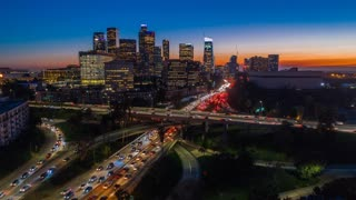 Cinematic urban aerial time lapse of downtown Los Angeles freeway traffic with the stunning city skyline and skyscrapers at twilight.