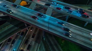 Cinematic urban aerial time lapse view of downtown Los Angeles freeways, highways and roads with traffic and night.