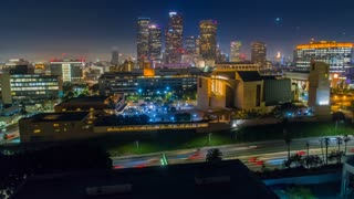 Cinematic urban aerial time lapse view of downtown Los Angeles with freeway traffic at night