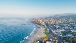 Cinematic urban aerial timelapse in motion or hyperlapse on a sunny morning flying over beautiful main beach towards downtown Laguna Beach with Heisler Park in view