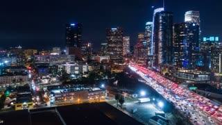 Cinematic urban aerial timelapse of downtown Los Angeles with traffic against the beautiful city skyline with sky scrapers in the evening.