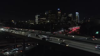 Cinematic urban aerial view of downtown Los Angeles freeway traffic with city skyline and tall buildings.