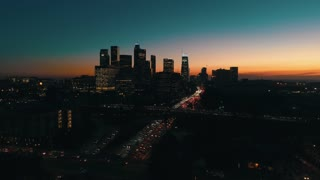 Cinematic urban aerial view of downtown Los Angeles skyline at night during rush hour with freeway traffic.