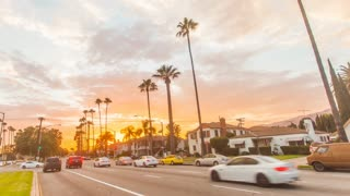 Cinematic urban timelapse in motion. Hyperlapse shot next to a city street during a stunning golden sunset with palm trees, neighborhood homes and cars in view