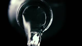 Clean water pours from the bottleneck of a glass bottle, close-up, black background, slow mo