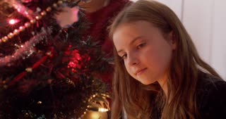 Close up of a young girl putting an ornament on the tree with her mother.