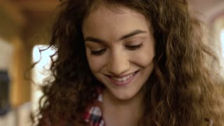 Close up of face of beautiful teenage girl with long curly hair at home