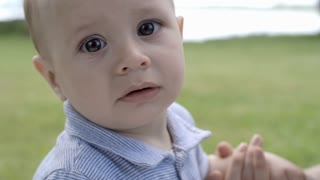 Close up of face of cute baby boy looking curiously at camera while unrecognizable mother holding his hand on summer day in park