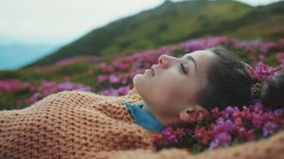 Close up of gorgeous young woman lying down in violet flowers, enjoying the moment. Freshness, aroma, natural beauty. Vintage look, light makeup, ponytail. Happy moments, joyful mood.