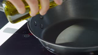 Close up of hands of male cook pouring olive oil into pan standing on working induction cooker