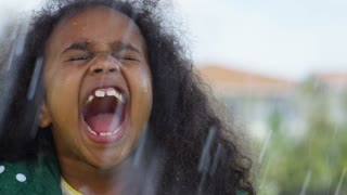 Close up of little girl with African-American girl with curly hair screaming in rain