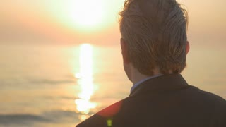 Close-up of mature businessman looking to the sun by the sea and thinking. Concept of middle-age man making his retirement's plans.