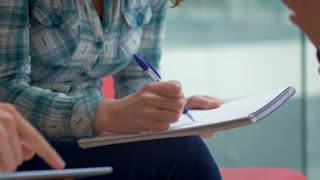 Close-up of young woman sitting and writing ideas in the notebook. Female entrepreneurs discussing on a business plan at the office.