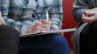 Close-up of young woman sitting and writing ideas in the notebook. Group of entrepreneurs making a business plan at the office.