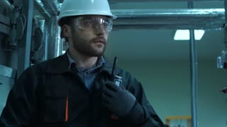 Close-up video of engineer in white hardhat, goggles and uniform inspecting pipes in laboratory and reporting to radio set