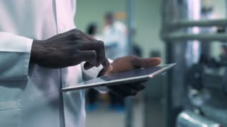 Close-up video of incognito Afro-American scientist hands in white lab coat holding a tablet and clicking on it while standing in laboratory