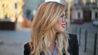 Close up view of a beautiful nerdy like attractive blonde woman in glasses with red lips looking right to the camera and smiling charmingly. Positive mood, being happy.