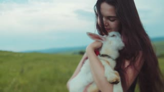 Close up view of a young pretty woman holding, kissing and petting white goat kid. Loving nature, cherish nature. Being happy, honesty. Beautiful landscape on the background.