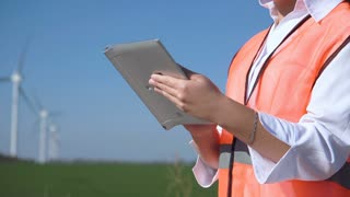Close up view of engineer working with digital tablet against wind turbine on sunny day