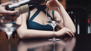 Close up view of waiter's hand pouring red wine in a glass for attractive young woman in a seductive dress, she smells wine, tastes it, pleased with the result thanks the waiter.