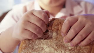 Close up view of young man's hands breaking bread loaf at table. Cuisine, customs and traditions. Hospitality, domestic kitchen. Indoors shooting.