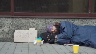 Close view of passerby giving money to sleeping homeless man