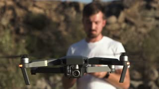 Close view of young man using black quadcopter with remote controller, movement stabilized shot