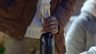 Closeup of hands of African man opening wine bottle with corkscrew at outdoor party