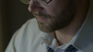 Closeup of serious man with stubble and eyeglasses typing on computer in the night