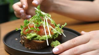 Closeup Of Smashed Avocado Toast Bread With Tomato And Greens