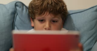 Closeup Of Young Boy In Front Of Tablet Screen Child Absorbed By Screen In 4K Candid Scene Of Kid Holding New Tech