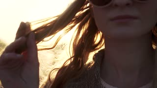 closeup portrait of a beautiful girl at dawn. a young woman touches hair. the sun's rays and glare. slow motion