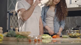 Closeup shot of fresh broccoli, bread and tomatoes on kitchen counter; man drinking wine and woman cooking in background. Focus on vegetables