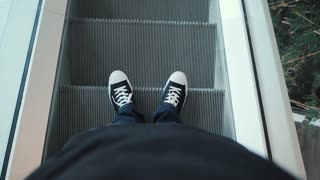 Closeup top view on man legs in sneakers traveler using moving escalator at airport terminal. Slow motion