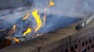 Closeup tracking shot of burning fire and charcoal in barbecue grill