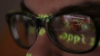 Code Reflection In Hackers Glasses. Hacker coding in dark room