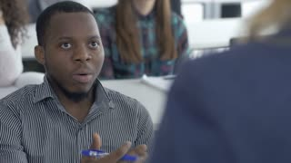 Confident university student discussing with a lecturer. Intelligent and motivated young man actively participating in classroom activity asking professor a question.