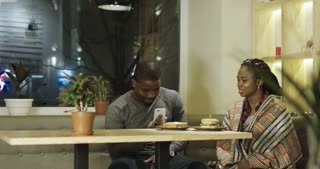 Content black man and woman on romantic date having coffee delivered by served. 4K shot on Red cinema camera.