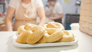 Cook put the fresh hot buns with sesame in the bakery