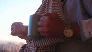 couple drinking coffee in new luxuary apartmant at top of building with sunset in background