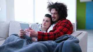 Couple is sitting on the couch sofa at home Look into the tablet